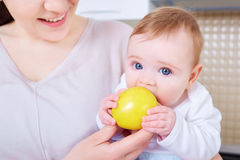 Baby isst gelben Apfel Kind lizenzfreie stockbilder