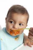 Baby isst Karotten von einem Löffel Stockfoto