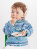 Baby isst Rosinen im Studio auf weißem Hintergrund Stockfoto