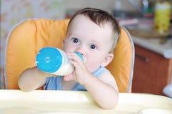 Baby isst von der kleinen Flasche Stockfoto