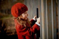 Baby 3 jaar met lang haar In een rood bevinden de baret zich en de laag op de straat in de zonneschijn, dichtbij de omheining stock afbeelding