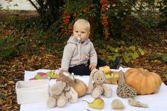 Baby 1 Jahre alt, werfend mit Kürbis und Spielwaren unter Bäumen I auf Stockbild