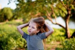 Baby 4 Jahre, mit blauen Augen, kleine Locken Eine wunderbare Zeit der Kindheit und des Abenteuers Warmes Sonnenlicht Hält Haar v lizenzfreie stockfotos
