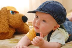 Baby in a jean cap. Next is a soft toy - dog Stock Images