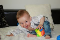 The baby in the jeans smiles and plays. A cute baby boy dressed in jeans and shirt smiles and plays stock photography
