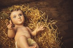 Baby Jesus Christmas card. Christmas greeting card, Baby Jesus vintage figurine in his crib Royalty Free Stock Photo
