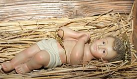 Baby Jesus is laid in the cradle in a manger. With folded hands praying Royalty Free Stock Photography