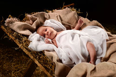 Baby Jesus on the Manger. Baby Jesus when born on a manger wrapped in swaddling clothes over dark background Stock Images