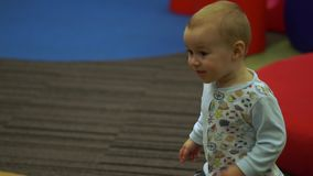 A baby joyfully runs in the children`s play area among the big geometric figures. Little cute boy joyfully runs in the children`s play area among the big stock footage