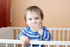 Baby keeps silent standing in white bed. 16 months baby keeps silent standing in white bed Stock Image