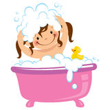 Baby kid girl bathing in bath tub and washing hair. A baby girl having bath in a bathtub with lot of soap lather and a rubber duck Stock Photo