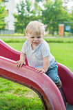 Baby kid standing on red slide Royalty Free Stock Photos