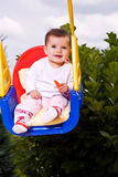 Baby on a kid swing 1 Stock Images