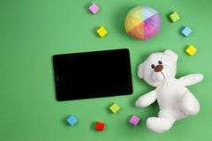 Baby kids toys background. Teddy bear, colorful cubes blocks and tablet computer on green background stock photo