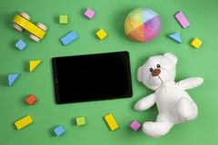 Baby kids toys background. Teddy bear, colorful cubes blocks, toy car and tablet computer on green background stock images