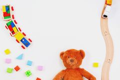 Baby kids toys background. Teddy bear, wooden train, colorful bricks on white table. Top view. Flat lay stock images
