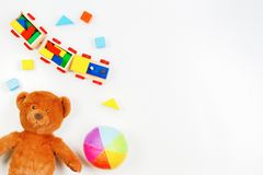 Baby kids toys background. Teddy bear, wooden train, colorful bricks on white table. Top view. Flat lay stock photo