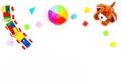 Baby kids toys background. Toy puppy, wooden train, colorful bricks on white table. Top view. Flat lay royalty free stock photos