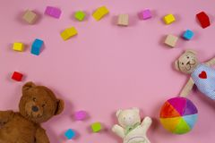 Baby kids toys frame with teddy bear, colorful wooden blocks on pink background. Top view. Baby kids toys frame with teddy bear, wooden blocks on pink background stock photo
