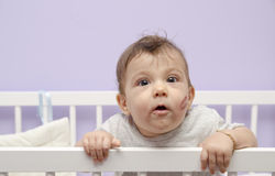 Baby and Kiss in crib Stock Image