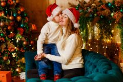 Baby kisses her mother on Christmas day. Seven-year-old boy hugging his mother, Christmas clothes royalty free stock photography