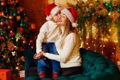 Baby kisses her mother on Christmas day. Seven-year-old boy hugging his mother, Christmas clothes stock images