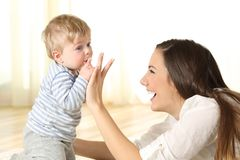 Baby kissing his mother finger. On the floor in a room royalty free stock images
