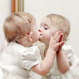 Baby kissing a Mirror Stock Image