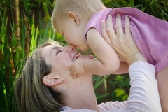 Baby kissing mom. A baby delights her mother by giving her a kiss on the nose as she holds her over her head Stock Photography