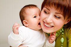 Baby kissing mother stock photography