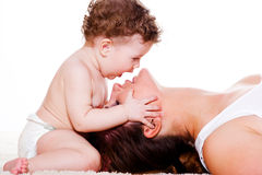 Baby kissing mother Stock Photos