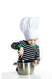 Baby kitchen chef cook. Baby boy in hat of the cook playing with kitchen accessories Royalty Free Stock Images