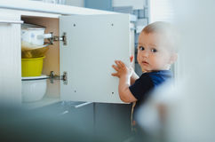 Baby in the kitchen. The child opens the door in the kitchen there is crockery, pans and bowls Stock Image