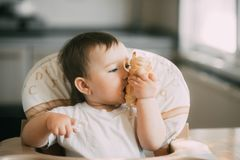 The baby in the kitchen greedily eats delicious creamy tubes filled with vanilla cream stock photos
