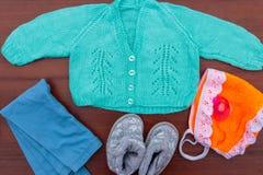 Baby Kleidung, Beuten und soother auf hölzernem Hintergrund Stockfoto
