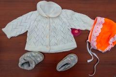 Baby Kleidung, Beuten und soother auf hölzernem Hintergrund Lizenzfreie Stockfotografie