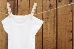 Baby-Kleidung, die in den Wäscheklammern auf waschender Linie hängt Stockfotos