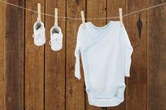 Baby-Kleidung, die in den Wäscheklammern auf waschender Linie hängt Lizenzfreies Stockfoto