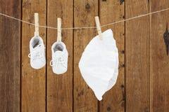 Baby-Kleidung, die in den Wäscheklammern auf waschender Linie hängt Lizenzfreie Stockfotografie