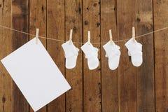 Baby-Kleidung, die in den Wäscheklammern auf waschender Linie hängt Stockfotografie