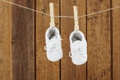 Baby-Kleidung, die in den Wäscheklammern auf waschender Linie hängt Lizenzfreie Stockbilder