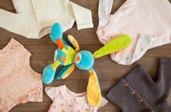 Baby-Kleidung und buntes Kaninchen-Spielzeug in einer Tischplatten-Ebenen-Lage-Anordnung auf hölzernem Hintergrund Browns Lizenzfreies Stockfoto