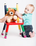 Baby Kneeling with Teddy Bear on Chair Stock Photo