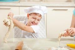 Baby kneten den Teig im Mehl lizenzfreie stockfotos