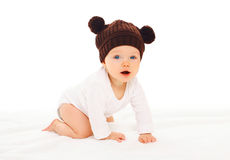 Baby in knitted brown hat with ears bears crawls on white Royalty Free Stock Image
