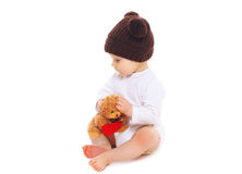 Baby in knitted brown hat with teddy bear toy sitting on white Royalty Free Stock Images