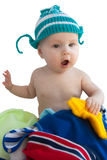 The baby in a knitted cap sits in a heap clothes Royalty Free Stock Photography