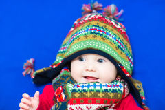 Baby in a knitted colorful hat and scarf on a blue blanket Royalty Free Stock Images