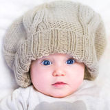 Baby in a knitted hat. Funny baby in a huge knitted hat wearing a warm sweater Royalty Free Stock Photo