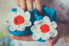 Baby knitted slippers in hands royalty free stock photos